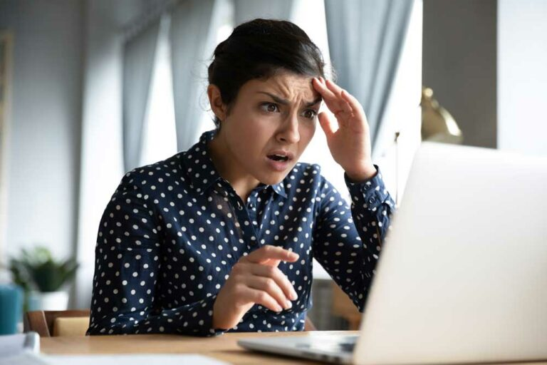 Corma Investigations | Shocked young woman looking at laptop screen feel terrified