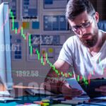 Corma Investigations | Broker in front of the computer on the background of numbers and charts